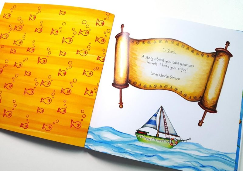An open book showing the personalised dedication on a scroll over a sailboat from the pirate adventure book The Golden Key