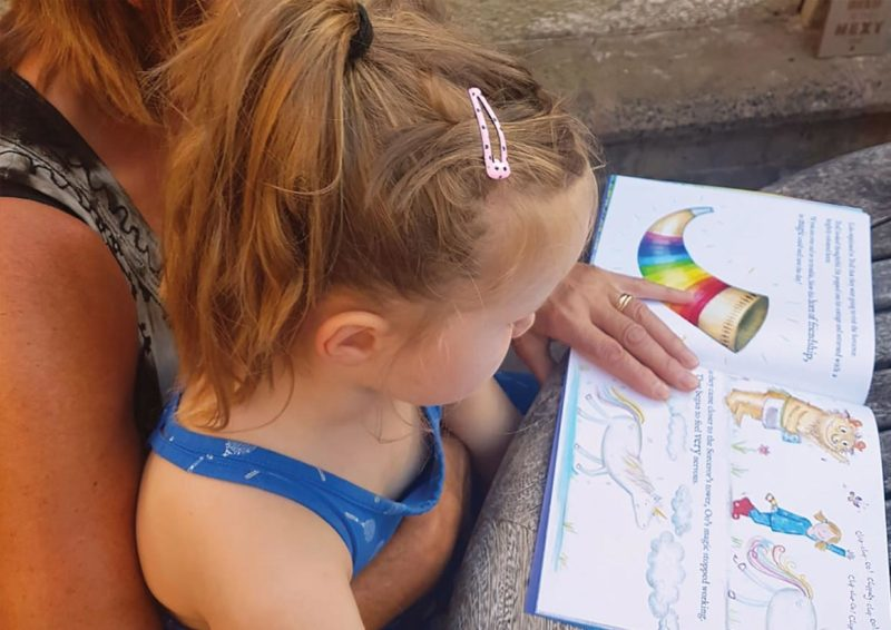 A girl reading her personalised copy of the Unicorn Oo book