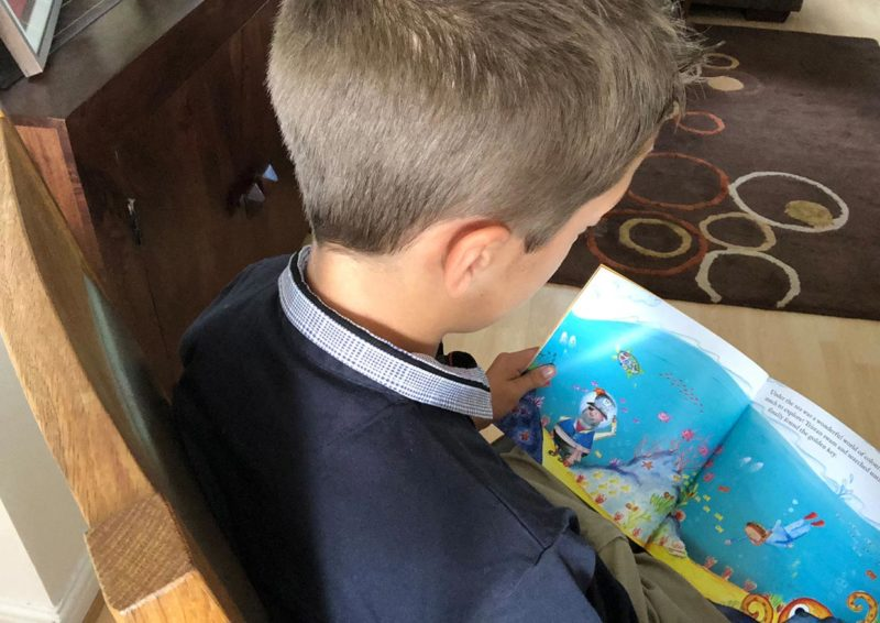 A boy reading his personalised book, The Golden Key.